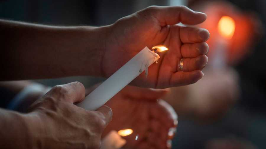 People light candles during a prayer and candle vigil organized by the El Paso city officials, after the shooting that left more than 20 people dead at the Cielo Vista Mall WalMart in El Paso, Texas, on August 4, 2019.