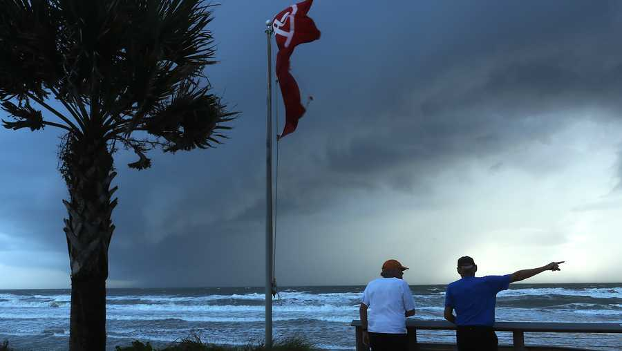 Two men observe a squall caused by hurricane Dorian which is looming in the Atlantic Ocean, on Sept. 3, 2019 in Ormond Beach, Florida.