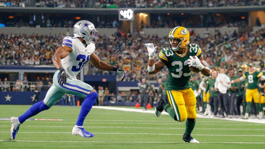 Green Bay Packers running back Aaron Jones (33) makes a waving gesture at Dallas Cowboys cornerback Byron Jones (31) as he rushes for a touchdown during the game between the Green Bay Packers and Dallas Cowboys on Oct. 6, 2019, at AT&T Stadium in Arlington, Texas.