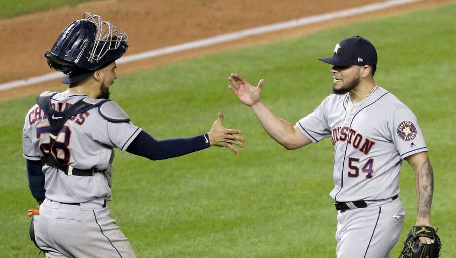Roberto Osuna #54 and Robinson Chirinos #28 of the Houston Astros celebrate their teams 4-1 win against the Washington Nationals in Game Three of the 2019 World Series at Nationals Park on October 25, 2019 in Washington, D.C.