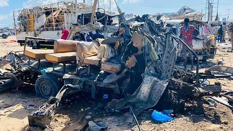 28 December 2019, Somalia, Mogadishu: The wreckage of a bus stands on the road at a checkpoint after a car bomb attack. Dozens were killed in a car bomb attack in Somalia's capital Mogadishu on Saturday, according to police.
