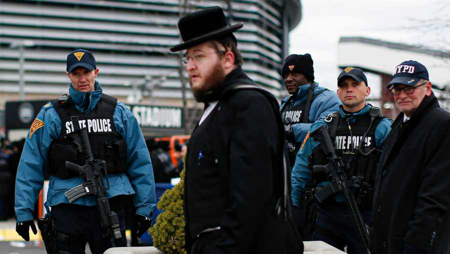 New Jersey State Police officers stand guard as people congregate at the MetLife Stadium to celebrate Siyum HaShas, the completion of the reading of the Babylonian Talmud, on Jan. 1, 2020, in East Rutherford, New Jersey. After the recent stabbing frenzy in New York's Rockland County, and a shooting earlier this month at a kosher deli in suburban New York's Jersey City that left six dead, the Jewish community is on edge.