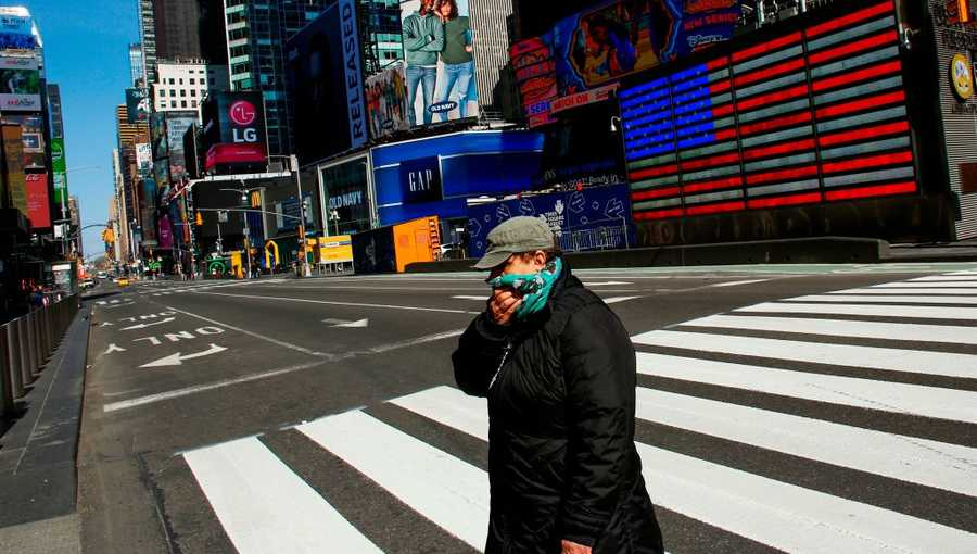 A woman cross  the street in Times Square as she covers her face on March 22, 2020 in New York City.