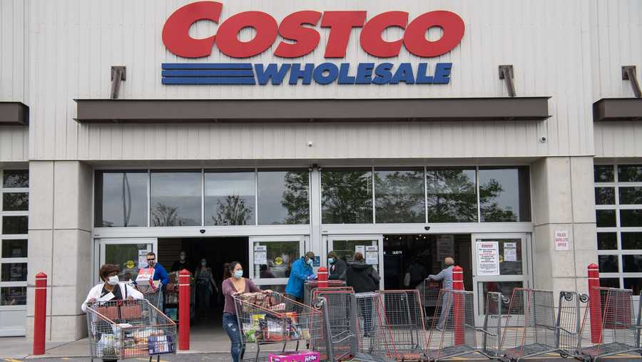 Shoppers walk out with carts from a Costco store in Washington, D.C., on May 5, 2020.