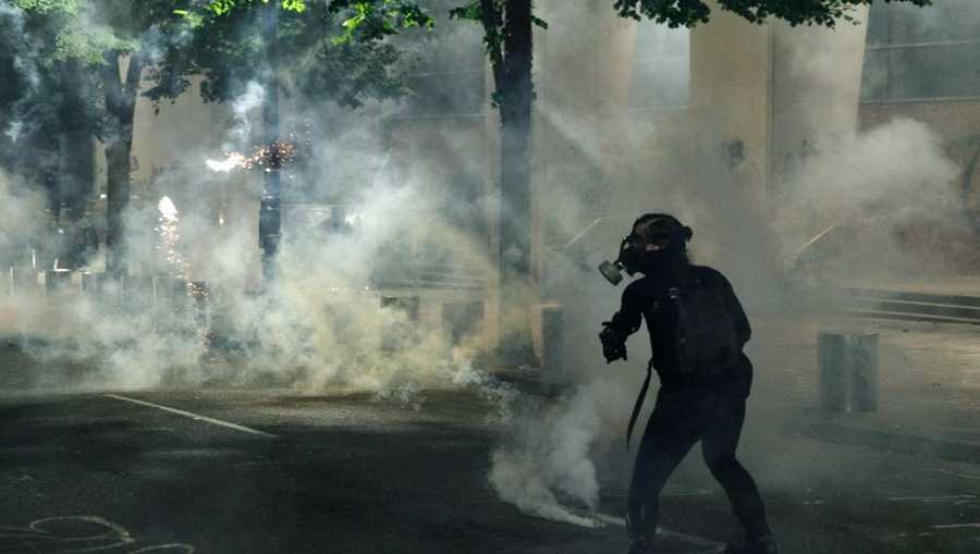 Tear gas and fireworks mix as Black Lives Matter supporters demonstrate in Portland, Oregon on July  4,  2020 for the thirty-eighth day in a row at Portland's Justice Center and throughout Portland, with a riot declared on July 5.