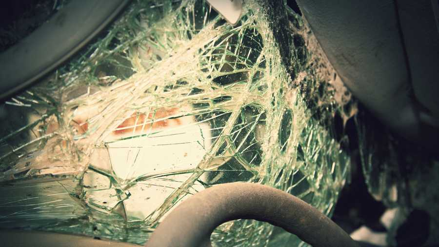 Close image of the steering wheel and shattered windshield of a wrecked vehicle.