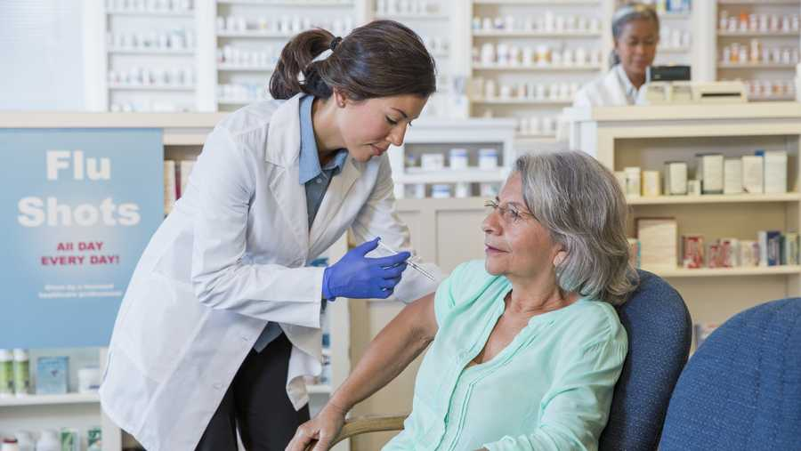 Pharmacist giving customer flu shot