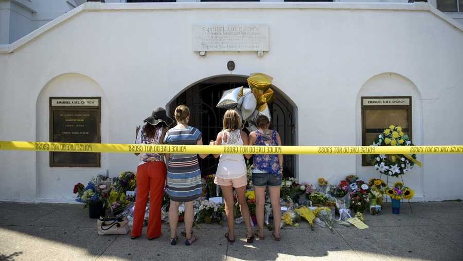 Mourners gather at a makeshift memorial outside the Emanuel AME Church in Charleston, South Carolina on June 18, 2015, after a mass shooting at the church the night before. Police detained the 21-year-old white supremacist after nine churchgoers were shot dead.