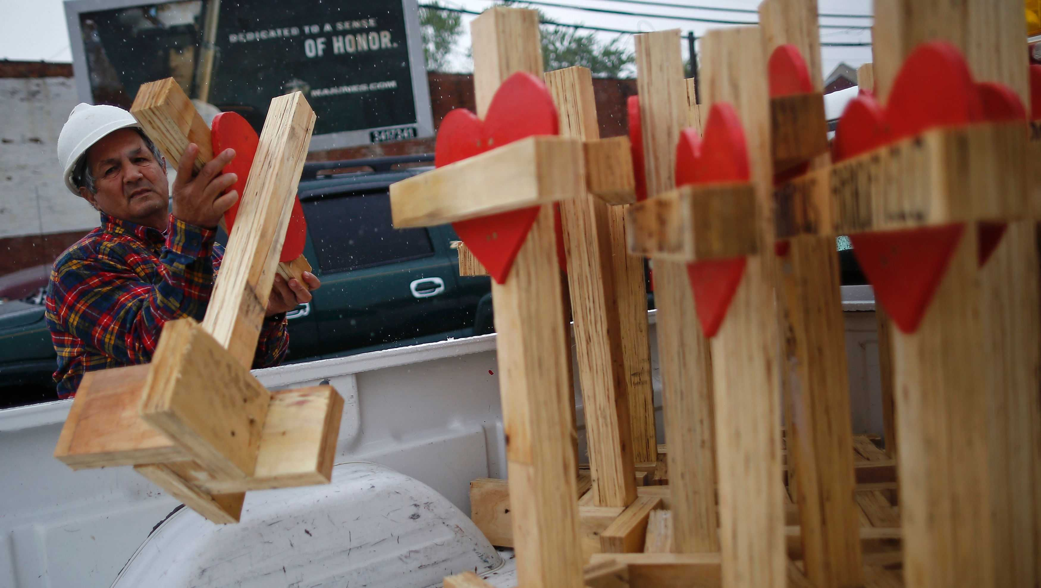 Greg Zanis unloads wooden crosses from the back of his truck at a planned prayer vigil and rally against violence in Chicago, Illinois on May 20, 2017.