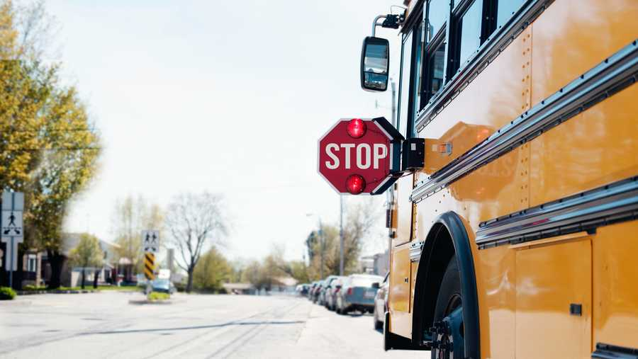 ellow School bus with stop sigh in the street with red light open. Photo was taken in Canada.