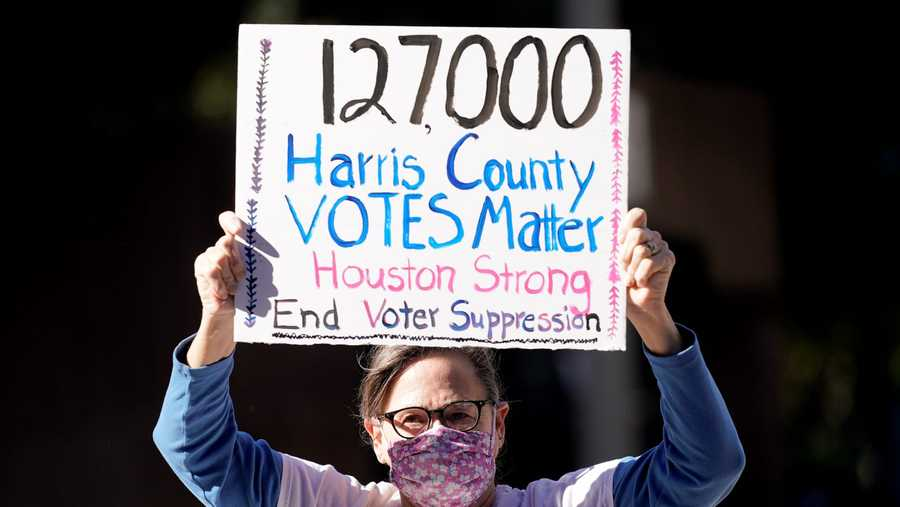 Demonstrator Gina Dusterhoft holds up a sign as she walks to join others standing across the street from the federal courthouse in Houston, Monday, Nov. 2, 2020.