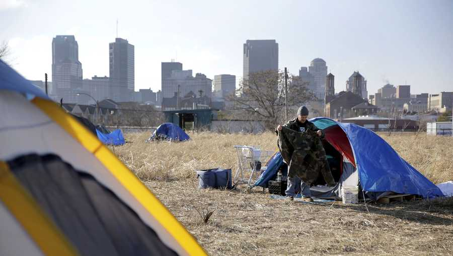 Terry, a homeless man who only gave his first name, cleans out his tent at a large homeless encampment Tuesday, Jan. 27, 2015, near downtown St. Louis. The city plans to tear down the camp down due to health and safety concerns, but Human Services director Eddie Roth says officials will work with those living in tents to help them find better alternatives. (AP Photo/Jeff Roberson)