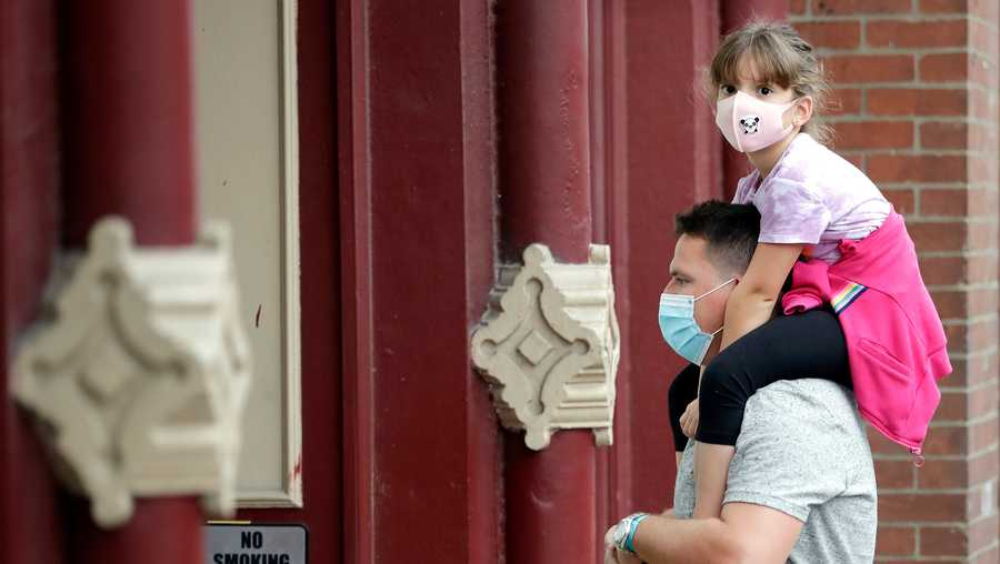 A man and a girl wear masks as they stop to hear a band outside a music venue Monday, June 29, 2020, in Nashville, Tenn. The Nashville Health Department has put in place a mask mandate beginning Monday to help battle the spread of the coronavirus.