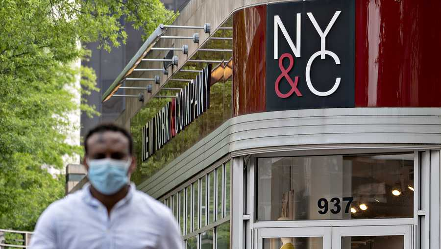 A pedestrian wearing a protective mask walks near a temporarily closed New York & Co. store in Silver Spring, Maryland, U.S., on Friday, June 5, 2020.