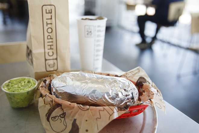 A chicken burrito, guacamole, bag of tortilla chips, and a drink are arranged for a photograph at a Chipotle Mexican Grill Inc. restaurant.