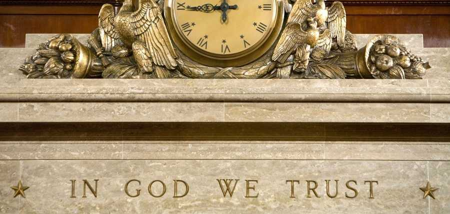 "In this file photo, a clock and the motto ""In God We Trust"" are seen over the Speaker's rostrum in the U.S. House of Representatives chamber in Washington, D.C."
