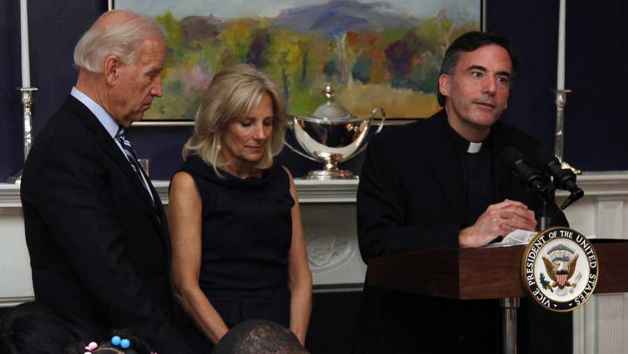 FILE - In this Nov. 22, 2010, file photo, Vice President Joe Biden, left, and his wife, Jill Biden, center, stand with heads bowed as the Rev. Kevin O'Brien says the blessing during a Thanksgiving meal for Wounded Warriors in Washington. O'Brien, the Jesuit priest who presided over an inaugural Mass for President Joe Biden, is under investigation for unspecified allegations and is on leave from his position as president of Santa Clara University in Northern California, according to a statement from the college's board of trustees.