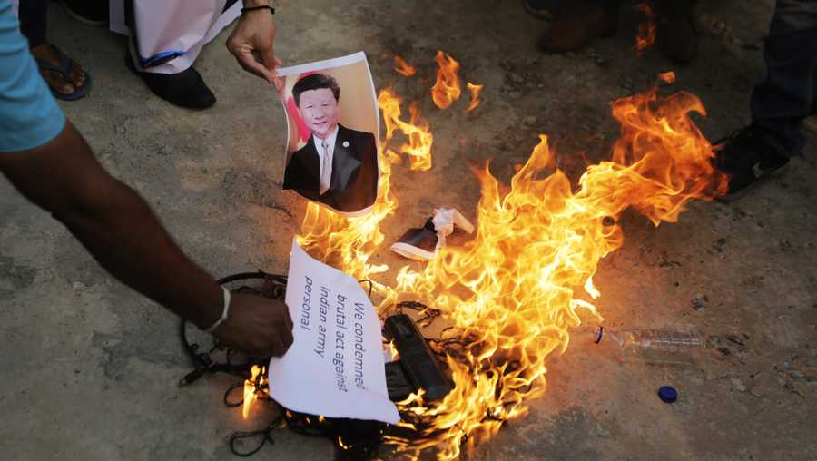 An Indian man burns a photograph of Chinese president Xi Jinping during a protest against China in Ahmedabad, India, Tuesday, June 16, 2020. At least three Indian soldiers, including a senior army officer, were killed in a confrontation with Chinese troops along their disputed border high in the Himalayas where thousands of soldiers on both sides have been facing off for over a month, the Indian army said Tuesday.