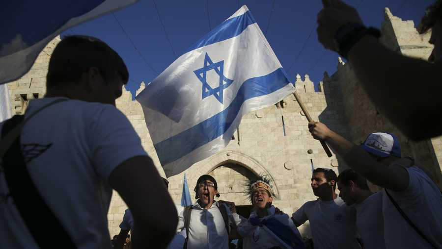 Israeli youth waves national flag outside the Old City's Damascus Gate in Jerusalem Wednesday, May 24, 2017, during Jerusalem Day which marks the 50th anniversary of Israel's capture of the city's eastern half from Jordanian control during the Six-Day War in 1967.