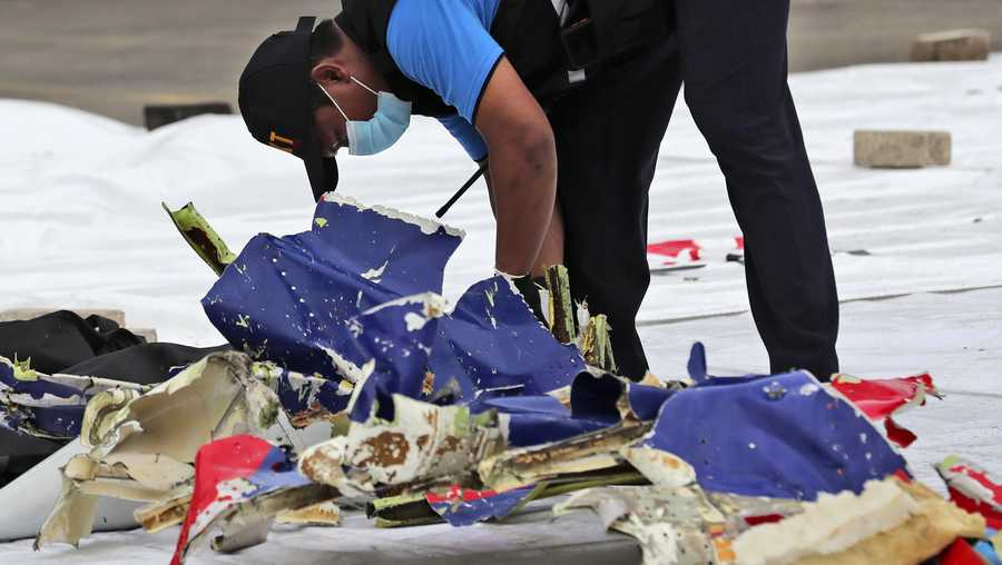 An investigator of Indonesian National Transportation Safety Committee inspects parts of Sriwijaya Air Flight 182 that crashed in the waters off Java Island, at Tanjung Priok Port in Jakarta, Indonesia, Sunday, Jan. 10, 2021.