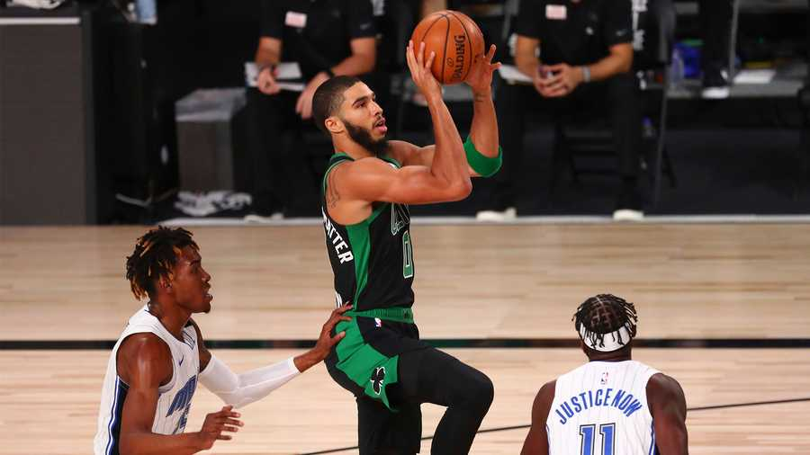 Boston Celtics forward Jayson Tatum (0) shoots against Orlando Magic forwards Wes Iwundu (25) and James Ennis III (11) during the first half of an NBA basketball game Sunday, Aug. 9, 2020, in Lake Buena Vista, Fla. (Kim Klement/Pool Photo via AP)