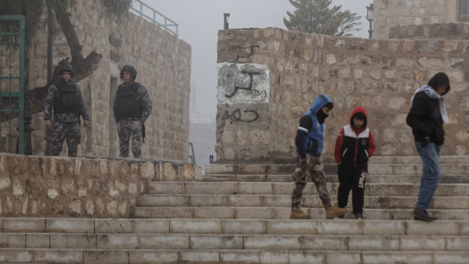 Jordanian security forces guard an entrance, left, as boys walk past in the morning mist in front of Karak Castle in the central town of Karak, about 140 kilometers (87 miles) south of the capital Amman, in Jordan Monday, Dec. 19, 2016.