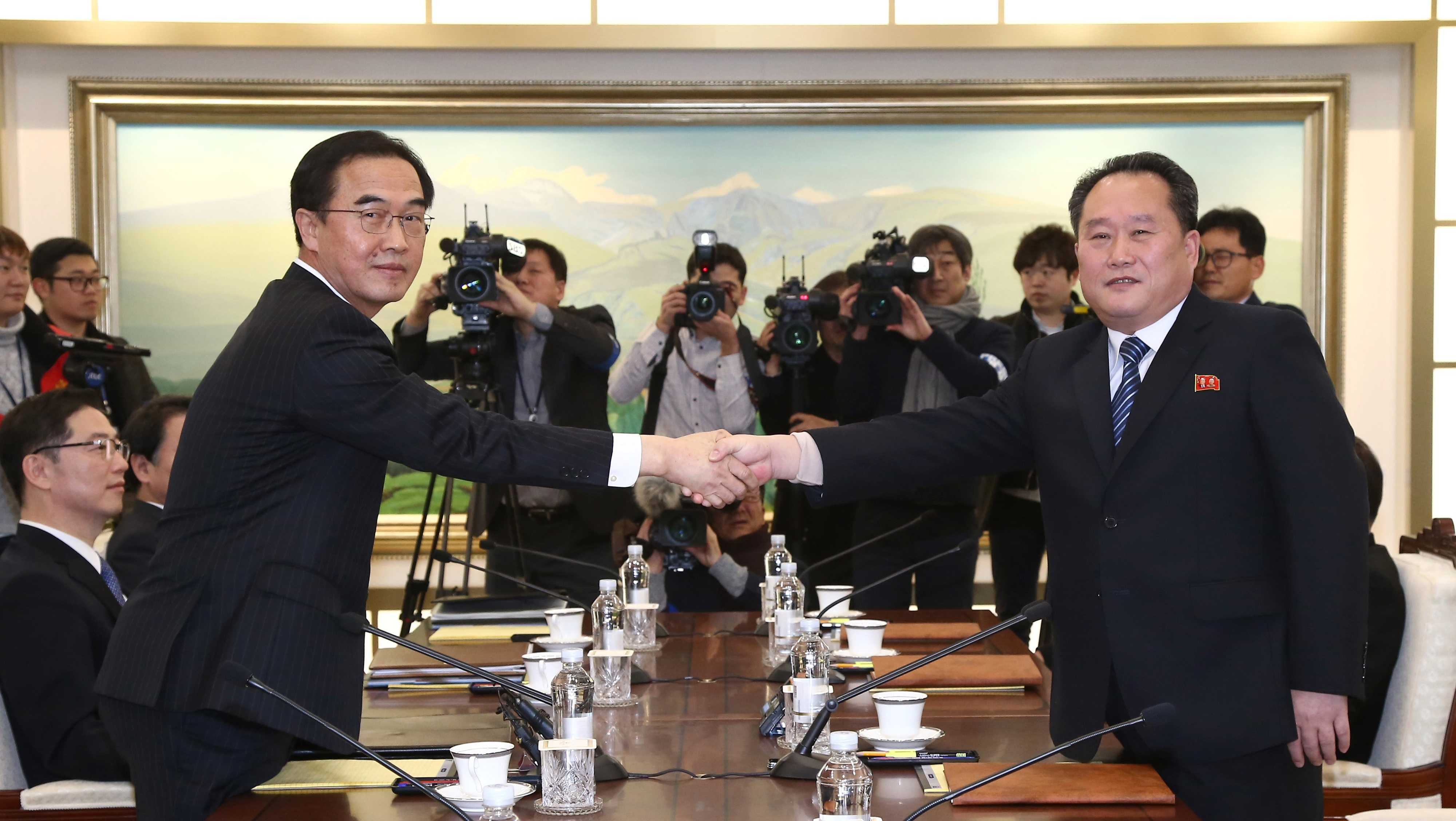 South Korean Unification Minister Cho Myoung-gyon, left, poses with head of North Korean delegation Ri Son Gwon while shaking hands during their meeting at the Panmunjom in the Demilitarized Zone in Paju, South Korea, Tuesday, Jan. 9, 2018. Senior officials from the rival Koreas said Tuesday they would try to achieve a breakthrough in their long-strained ties as they sat for rare talks at the border to discuss how to cooperate in next month's Winter Olympics in the South and other issues.