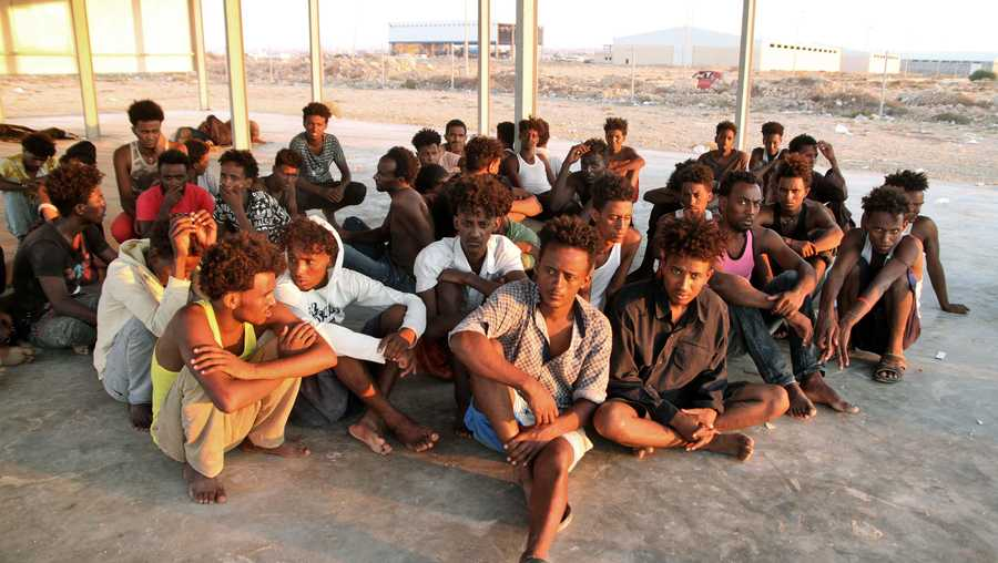 Rescued migrants sit on the coast of Khoms, about 60 miles from the Libyan capital Tripoli, on July 26, 2019. More than 100 migrants were missing after their boat sank off the coast of Libya in what might be the worst tragedy in the Mediterranean this year, aid agencies said.