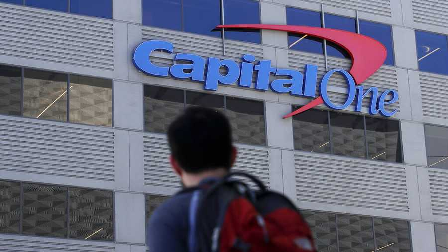 In this July 16, 2019, photo, a man walks across the street from a Capital One location in San Francisco. Capital One says a hacker got access to the personal information of over 100 million individuals applying for credit.