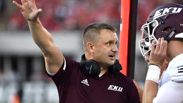 Eastern Kentucky head coach Mark Elder, left, talks with quarterback Austin Scott during the first half of an NCAA college football game against Louisville in Louisville, Ky., Saturday, Sept. 7, 2019. (AP Photo/Timothy D. Easley)