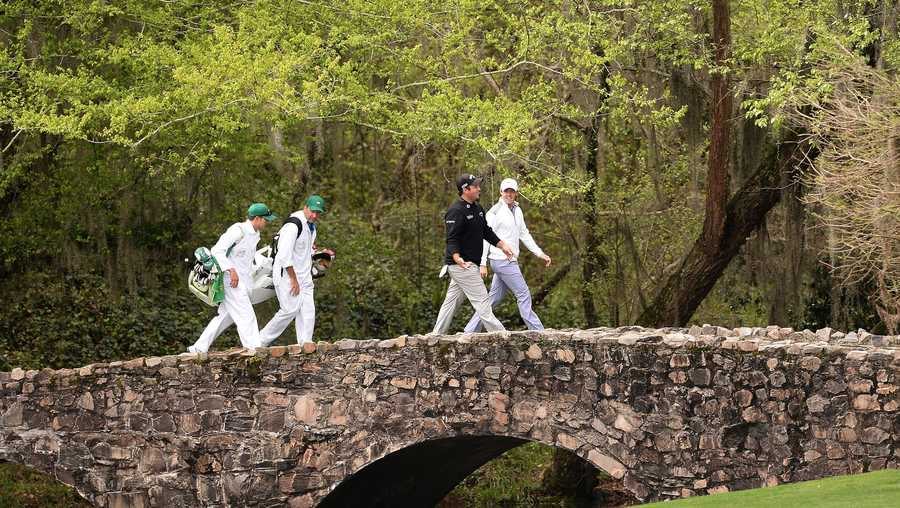 Rory McIlroy of Northern Ireland (R) and Patrick Reed of the US walk across a bridge during a practice round for the Masters tournament at the Augusta National Golf Club Augusta, Georgia, on April 8, 2014