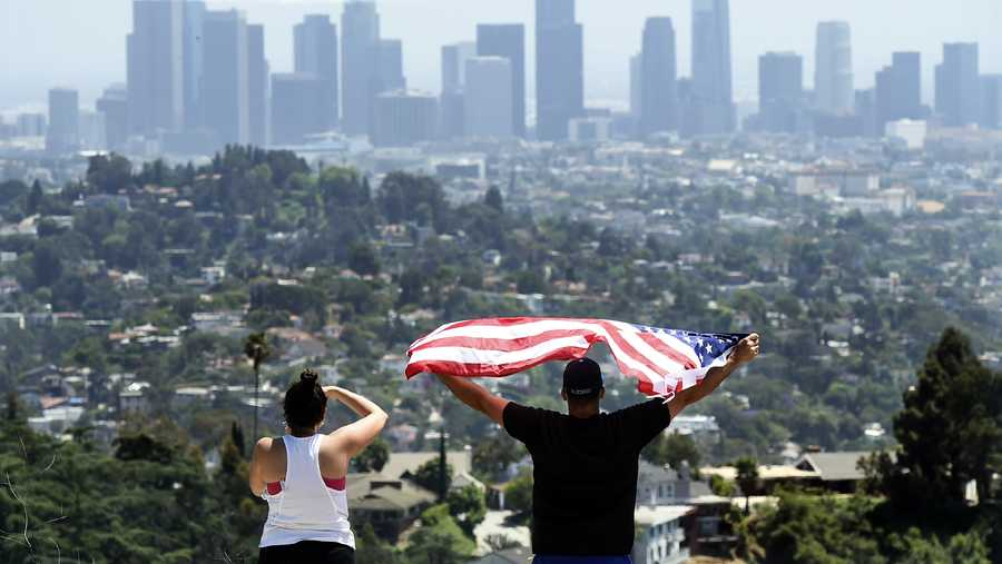 in this may 15, 2020, file photo, a couple salute the united states air force thunderbirds who fly over downtown los angeles to honor frontline covid 19 responders at griffith park in los angeles