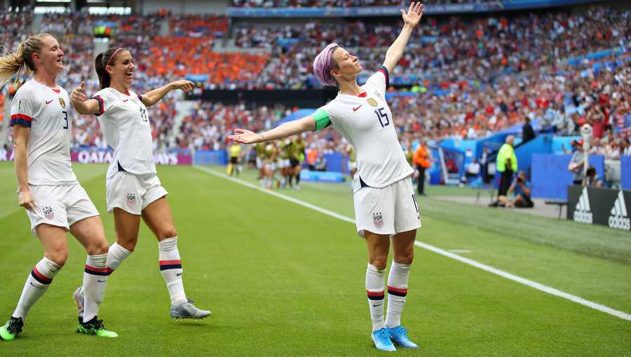 Megan Rapinoe of the USA celebrates after scoring her team's first goal with team mates Samantha Mewis and Alex Morgan during the 2019 FIFA Women's World Cup France Final match between The United States of America and The Netherlands at Stade de Lyon on July 07, 2019 in Lyon, France.
