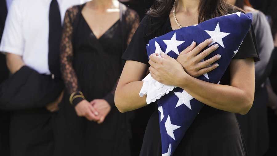 File photo: woman holds a folded American flag at a funeral.