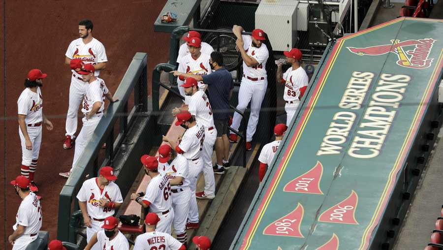 In this July 24, 2020, file photo, members of the St. Louis Cardinals wait to be introduced before the start of a baseball game against the Pittsburgh Pirates in St. Louis.