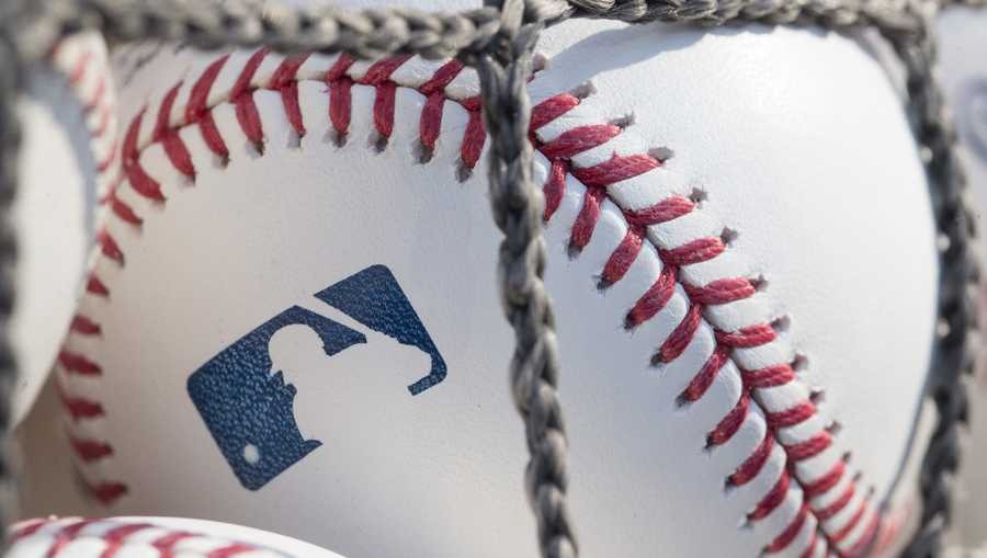A close-up baseball with the MLB logo is shown.