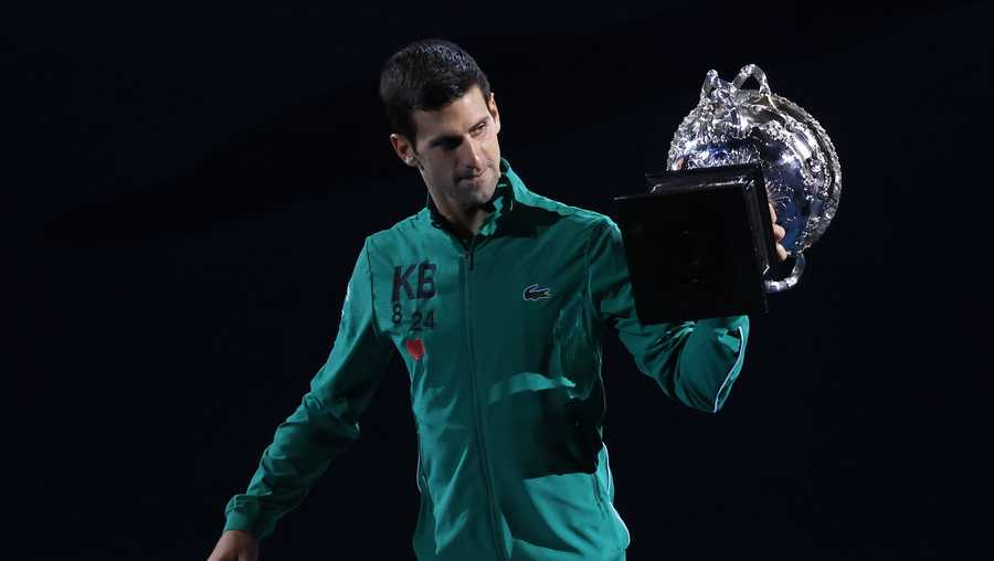 Serbia's Novak Djokovic carries the Norman Brookes Challenge Cup around Rod Laver Arena after defeating Austria's Dominic Thiem in the men's singles final of the Australian Open tennis championship in Melbourne, Australia, early Monday, Feb. 3, 2020.