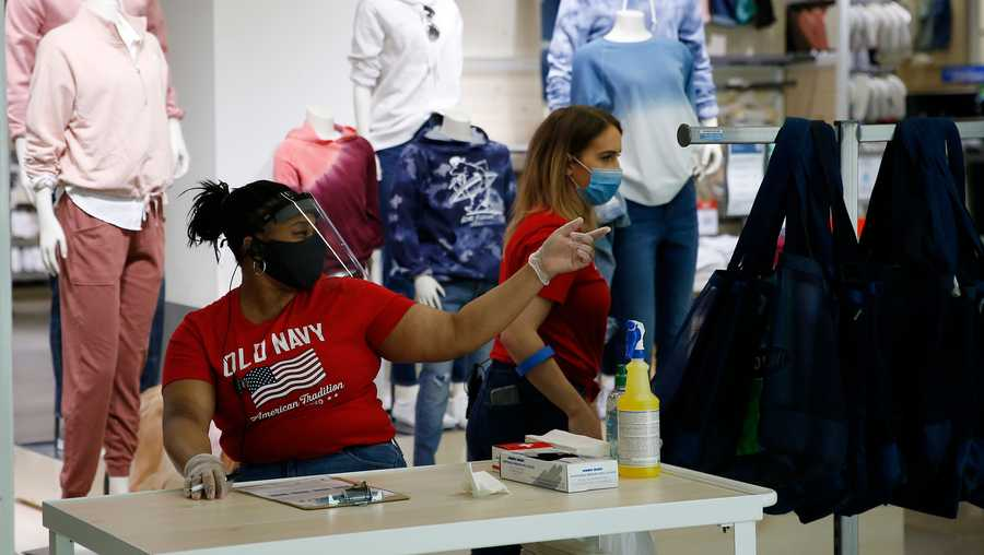 An Old Navy employee sits at the front and keeps track of how many people are inside the store at CambridgeSide in Cambridge, MA during the first day of Phase 2 of re-opening in Massachusetts on June 8, 2020.
