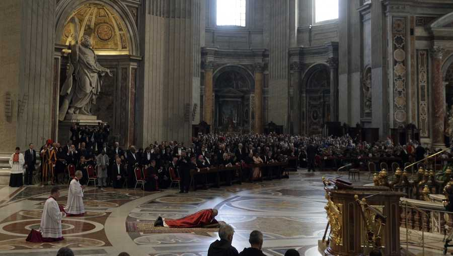 Pope Francis, center, lies down in prayer during the Good Friday Passion of Christ Mass inside St. Peter's Basilica, at the Vatican, Friday, April 14, 2017.