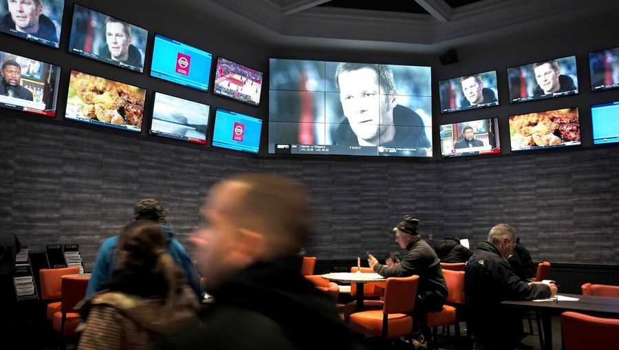 FILE - In this Jan. 28, 2019, file photo, patrons visit the sports betting area of Twin River Casino in Lincoln, R.I. Rhode Island has launched mobile sports betting. The Rhode Island state revenue department says the mobile application launched Wednesday, Sept. 4, 2019, at Twin River Casino. (AP Photo/Steven Senne, File)