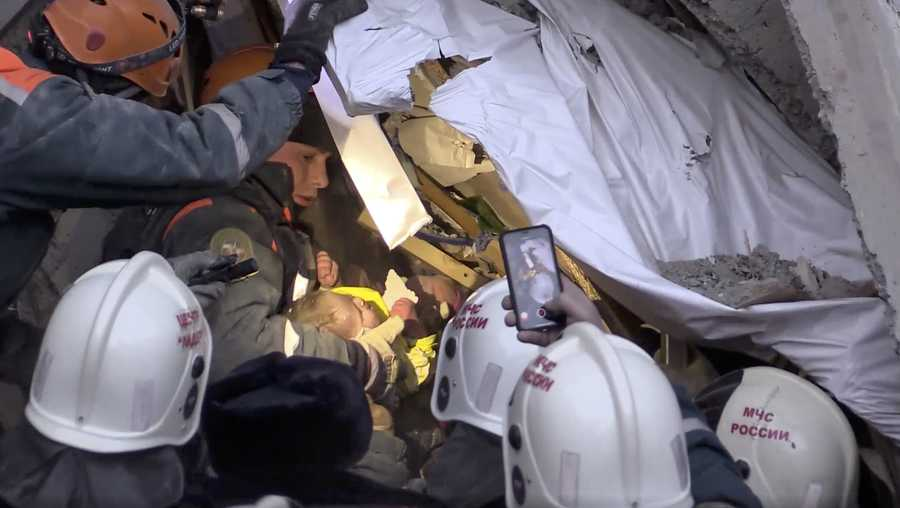 This photo provided by the Russian Emergency Situations Ministry taken from tv footage shows Emergency Situations employees save a 10 month old baby at the scene of a collapsed section of an apartment building, in Magnitigorsk, a city of 400,000 about 870 miles southeast of Moscow, Russia, Tuesday, Jan. 1, 2019.
