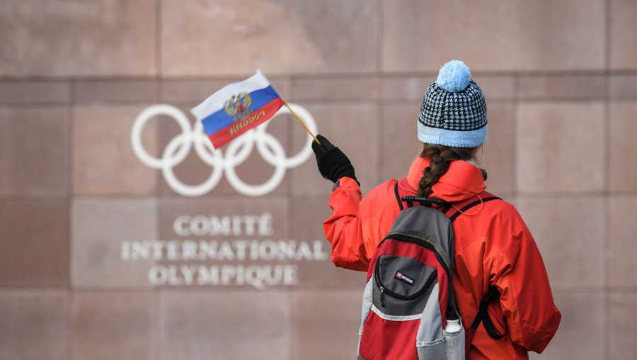 A supporter waves a Russian flag in front of the logo of the International Olympic Committee (IOC) at their headquarters on December 5, 2017 in Pully near Lausanne.