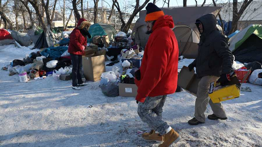 Felipe, center, and George Arroyo, right, look for boxes to burn inside a garbage can to keep warm at a makeshift camp on Roosevelt Road near the Dan Ryan Expressway in Chicago.