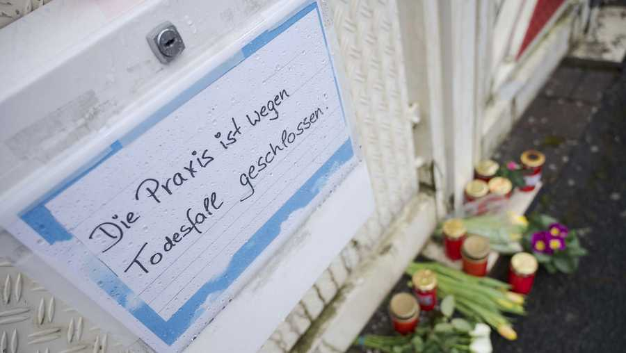 Flowers and candles laid outside the practice of the doctor killed in the explosion in Enkenbach-Alsenborn, Germany.