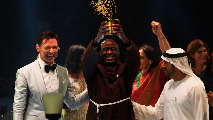 Kenyan teacher Peter Tabichi, center, actor Hugh Jackman, left, and Dubai crown prince Sheikh Hamdan bin Mohammed Al Maktoum react after Tabichi won the $1 million Global Teacher Prize in Dubai, United Arab Emirates.