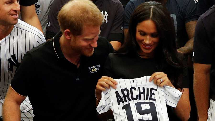 Prince Harry and Meghan Markle pose with a tiny jersey gifted by the New York Yankees.
