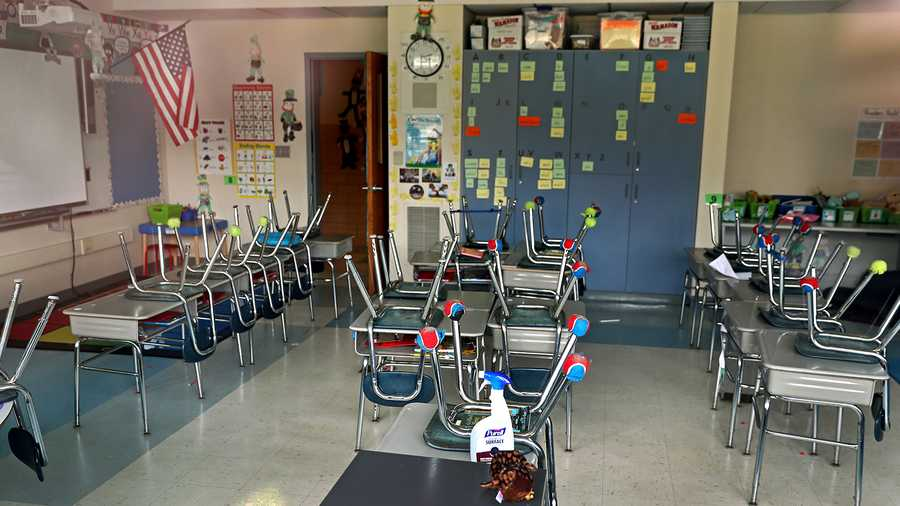 An empty classroom at the Grace Farrar Cole School in Norwell, MA with a bottle of sanitizer left on a desk on April 21, 2020.
