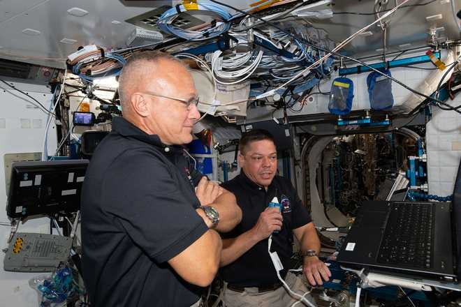 NASA astronauts Doug Hurley (foreground) and Bob Behnken, who flew the Crew Dragon spacecraft to the International Space Station during SpaceX Demonstration Mission-2, are pictured briefing mission controllers about their experience in the new vehicle on June 1, 2020.