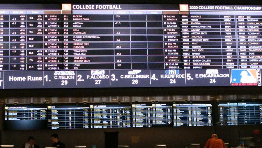 In this June 27, 2019 photo, a gambler places a bet at the new sportsbook at Bally's casino in Atlantic City, N.J. New Jersey surpassed Nevada in terms of sports betting volume in May, taking the national lead for the first time. (AP Photo/Wayne Parry)