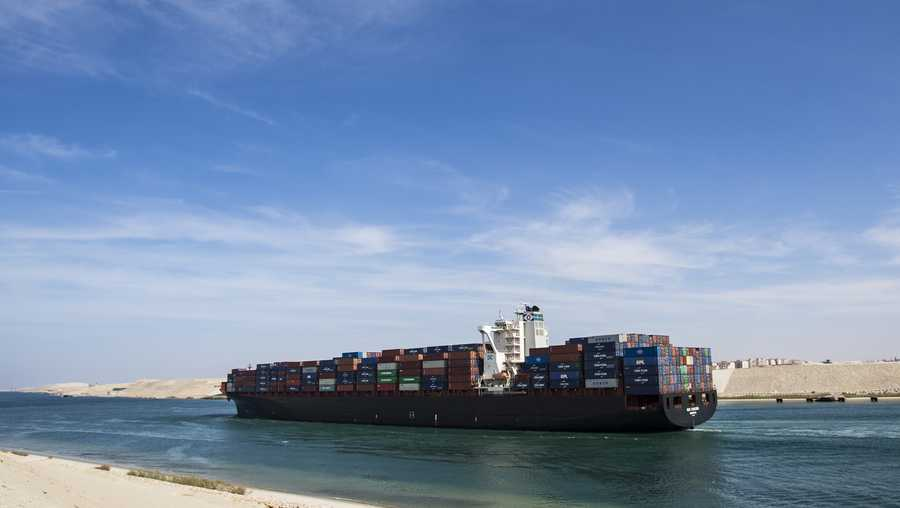 FILE- A container ship sails in Suez Canal, during the 150th anniversary of the Suez Canal.
